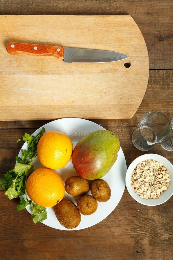 Σε έναν ξύλινο πίνακα σε ένα άσπρο πιάτο πορτοκάλια ακτινίδιων μάγκο στο υπόβαθρο ένας ξύλινος τέμνων πίνακας και ένα μαχαίρι Κάθ στοκ φωτογραφία