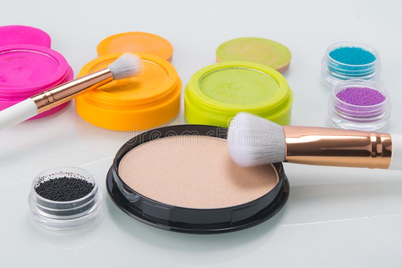 Σε έναν φωτεινό πίνακα, τα στοιχεία για το makeup, τις ζωηρόχρωμες σκιές, τη σκόνη και τις βούρτσες για να ισχύσει στοκ φωτογραφίες με δικαίωμα ελεύθερης χρήσης