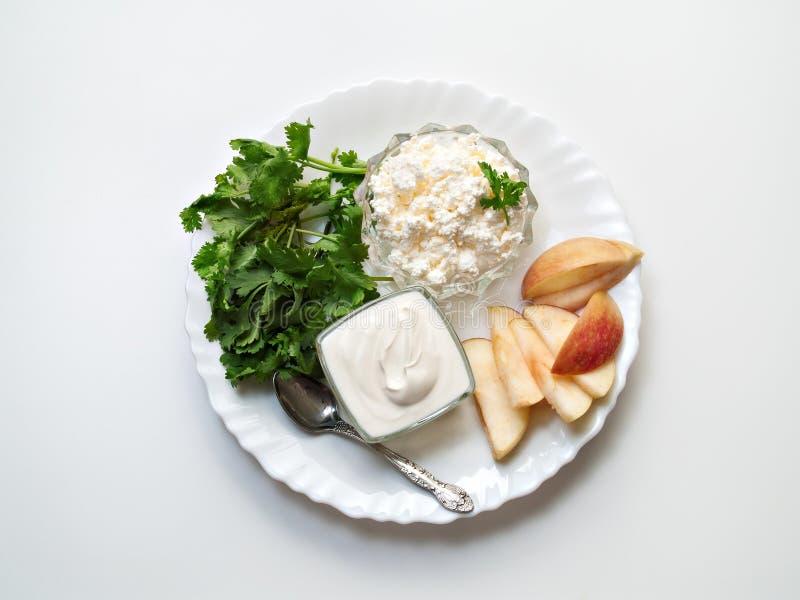 Σε ένα άσπρο υπόβαθρο υπάρχει ένα πιάτο με το τυρί εξοχικών σπιτιών, ξινό στοκ εικόνες