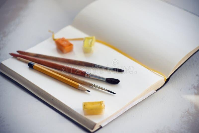 Σε ένα ανοικτό σημειωματάριο είναι βούρτσες, μολύβι και watercolors στους δοκιμαστικούς σωλήνες στοκ φωτογραφία με δικαίωμα ελεύθερης χρήσης