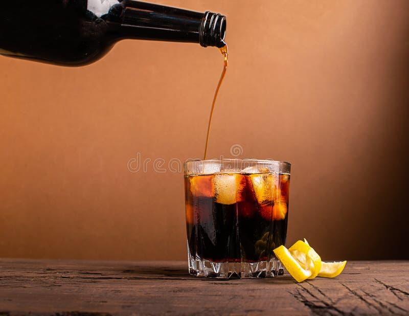Σε ένα γυαλί τους κύβους πάγου που χύνονται το κονιάκ ουίσκυ Ισχυρό οινοπνευματώδες ποτό σε ένα σκοτεινό υπόβαθρο r r στοκ φωτογραφία με δικαίωμα ελεύθερης χρήσης