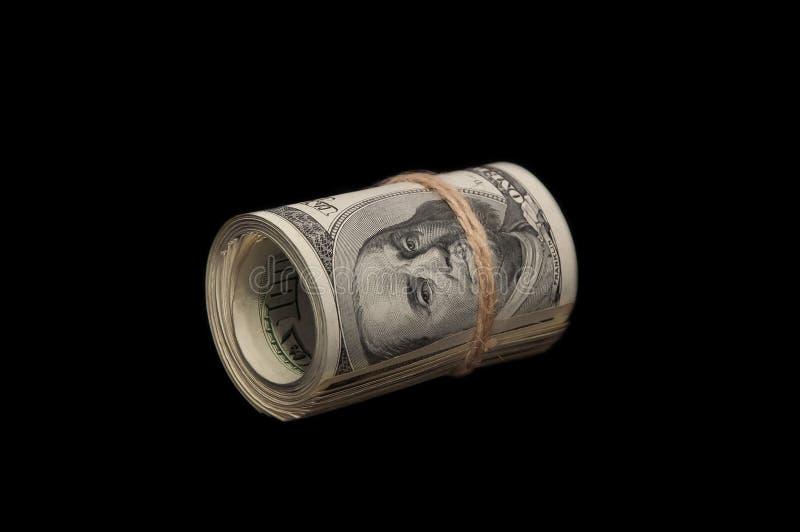 Σε ένα μαύρο υπόβαθρο, ένας ρόλος των λογαριασμών εκατό δολαρίων έδεσε με ένα σχοινί Βρίσκεται οριζόντια διαγωνίως στοκ εικόνες