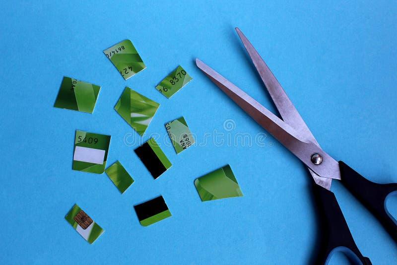 Σε ένα μπλε το υπόβαθρο βρίσκεται μια πλαστική κάρτα που κόβεται σε πολλά κομμάτια στοκ εικόνες