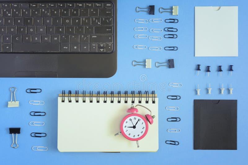 Σε ένα μπλε υπόβαθρο, οι προμήθειες σημειωματάριων και γραφείων τακτοποιήθηκαν τακτοποιημένα Στην ανοικτή σελίδα του σημειωματάρι στοκ φωτογραφία