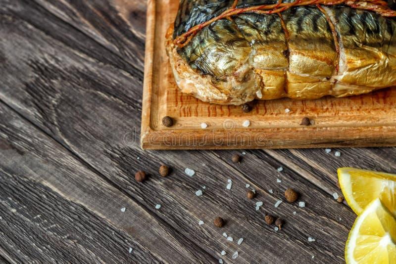 Σε ένα ξύλινο υπόβαθρο, ένα καπνισμένο ψάρι με το κρεμμύδι φετών λεμονιών και μια δέσμη των πρασίνων στοκ εικόνες