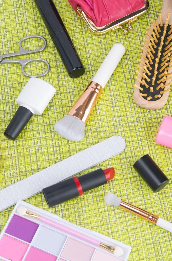 Σε ένα πράσινο υπόβαθρο, εργαλεία για το μανικιούρ και makeup, στιλβωτικές ουσίες καρφιών, το ψαλίδι, κόκκινο κραγιόν, βούρτσες σ στοκ εικόνες με δικαίωμα ελεύθερης χρήσης