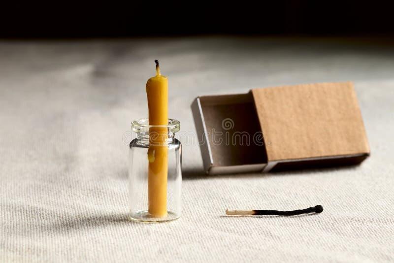 Σε ένα σκοτάδι το δωμάτιο στον πίνακα είναι ένα εκλείψας κερί Κενό ένα σπιρτόκουτο και στο τέλος μια αντιστοιχία έκαψαν για να συ στοκ φωτογραφία με δικαίωμα ελεύθερης χρήσης