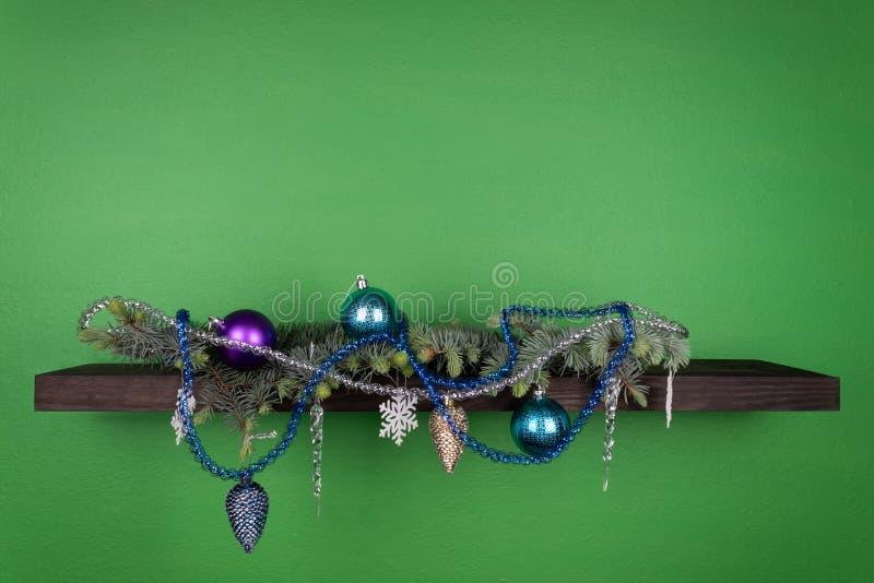 Σε ένα σκοτεινός-χρωματισμένο ράφι που συνδέεται με έναν πράσινο τοίχο, οι κωνοφόροι κλάδοι είναι διακοσμημένοι με τα παιχνίδια τ στοκ φωτογραφία με δικαίωμα ελεύθερης χρήσης