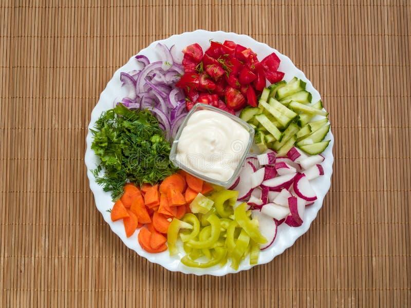 Σε ένα στρογγυλό άσπρο πιάτο λεπτά - τεμαχισμένα λαχανικά και ένα φλυτζάνι W στοκ φωτογραφία με δικαίωμα ελεύθερης χρήσης