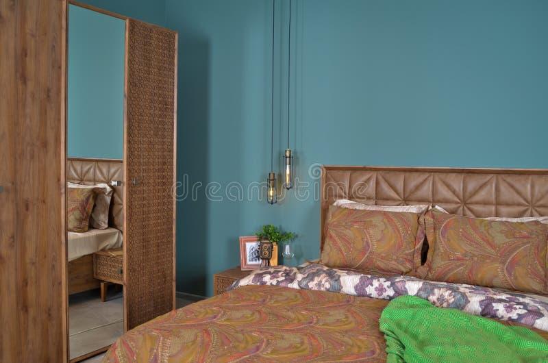 Σε ένα σύγχρονο κρεβάτι κρεβατοκάμαρων, τα μαξιλάρια και τους λαμπτήρες πλευρών στοκ φωτογραφία