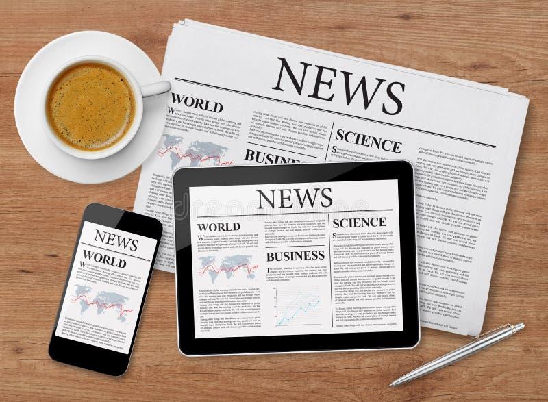 Σελίδα ειδήσεων στην ταμπλέτα, το κινητές τηλέφωνο και την εφημερίδα στοκ εικόνες