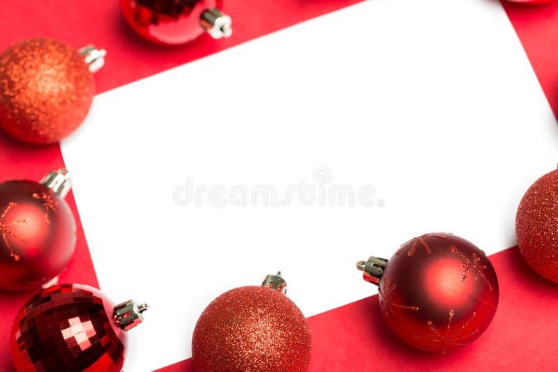 Σελίδα που περιβάλλεται άσπρη από τα μπιχλιμπίδια Χριστουγέννων στοκ εικόνα