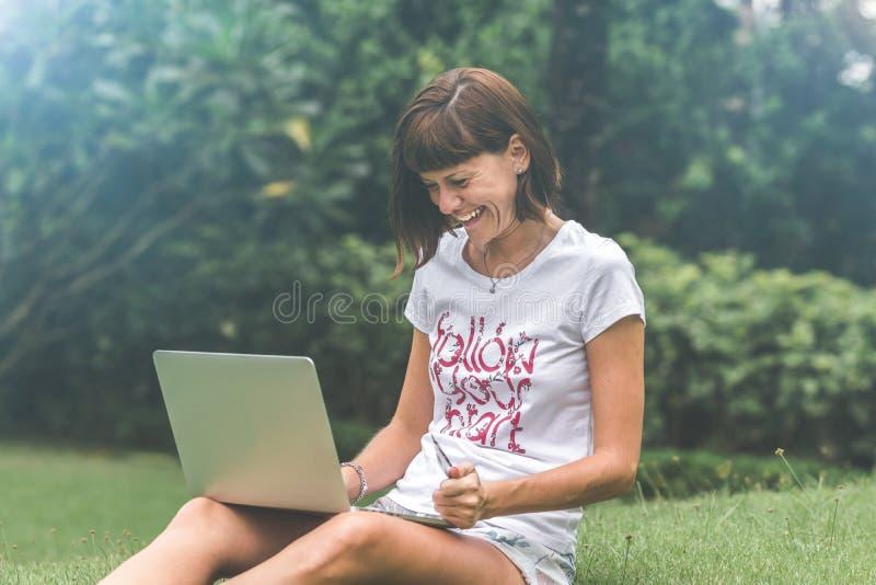 Σε απευθείας σύνδεση έννοια αγορών γυναικών Γυναίκα στο πράσινο πάρκο με το σύγχρονο lap-top Νησί του Μπαλί στοκ εικόνα με δικαίωμα ελεύθερης χρήσης