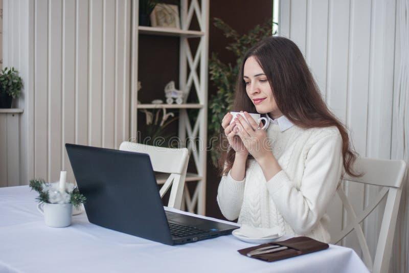 Σε απευθείας σύνδεση εργασία ένα κορίτσι πίσω από τα lap-top και στοκ εικόνα με δικαίωμα ελεύθερης χρήσης