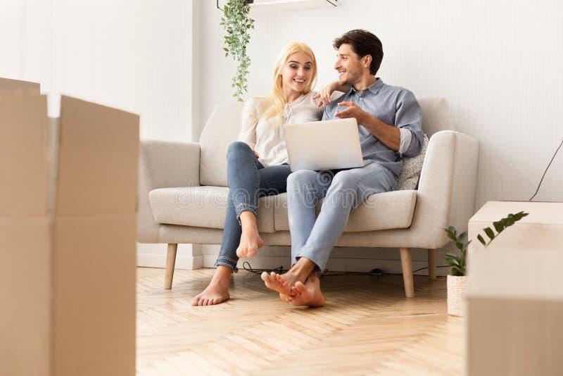 Σε απευθείας σύνδεση συνεδρίαση επίπλων αγοράς ζεύγους στον καναπέ στο νέο διαμέρισμα στοκ φωτογραφίες με δικαίωμα ελεύθερης χρήσης