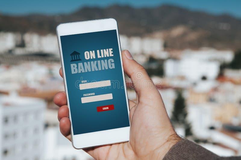 Σε απευθείας σύνδεση τραπεζικές εργασίες app σε ένα κινητό τηλέφωνο Χέρι ατόμων που κρατά το τηλέφωνο στην πόλη στοκ εικόνες με δικαίωμα ελεύθερης χρήσης