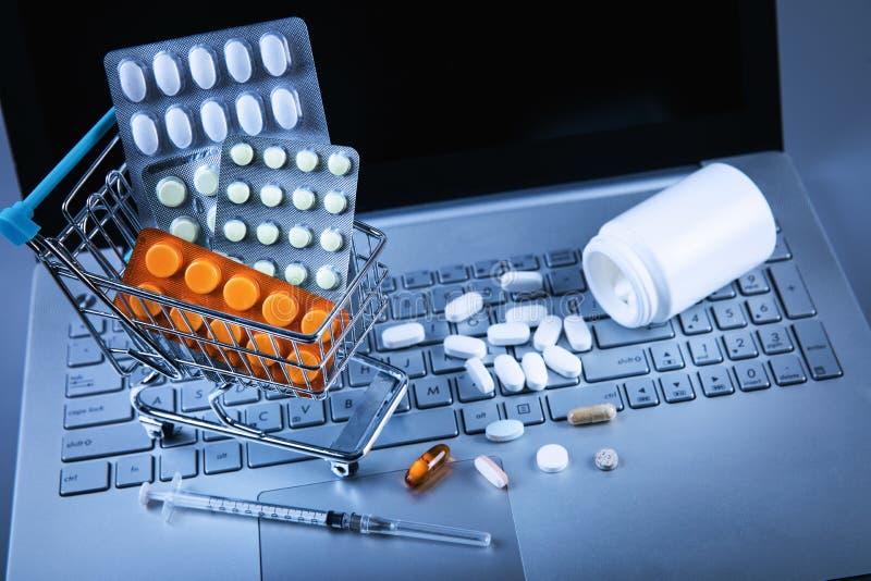 Σε απευθείας σύνδεση φαρμακείο - κάρρο αγορών με τα χάπια στο πληκτρολόγιο υπολογιστών στοκ φωτογραφίες