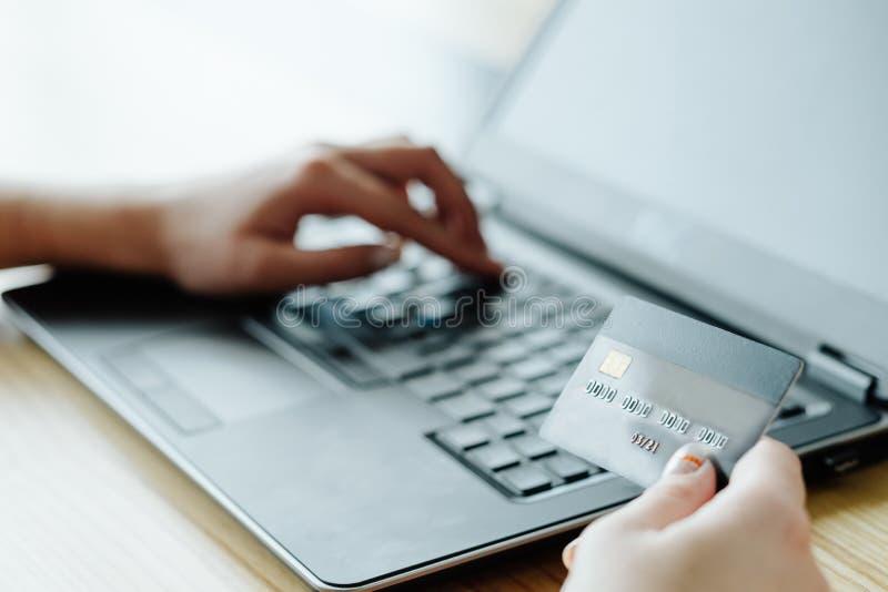 Σε απευθείας σύνδεση lap-top πιστωτικών καρτών δακτυλογράφησης γυναικών δανείου χρημάτων στοκ φωτογραφία