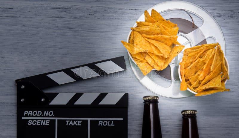 Σε ελαφρύ υπόβαθρο, δύο κάδους των nachos και της μπύρας, την ταινία και το διπλάσιο για τη μαγνητοσκόπηση στοκ εικόνα με δικαίωμα ελεύθερης χρήσης