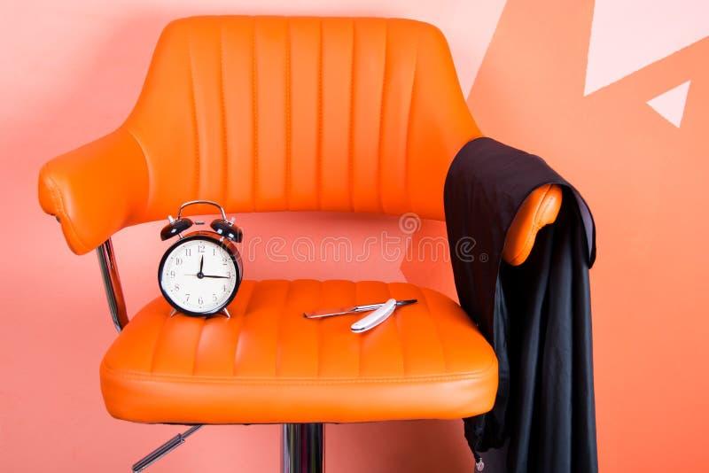 σε μια πορτοκαλιά πολυθρόνα δέρματος, βρίσκεται ένα ξυπνητήρι, ένα μαχαίρι και μια ποδιά για την τέμνουσα τρίχα στοκ φωτογραφία