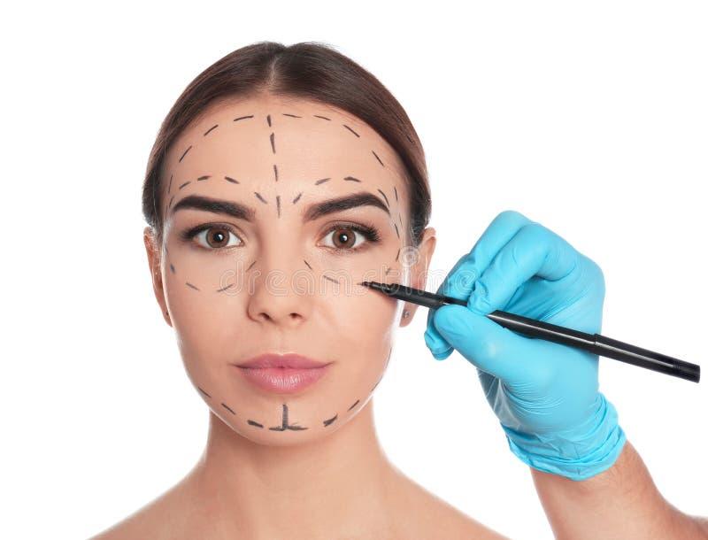 Σημάδια σχεδίων γιατρών στο πρόσωπο της γυναίκας για τη λειτουργία αισθητικής χειρουργικής στοκ εικόνα με δικαίωμα ελεύθερης χρήσης