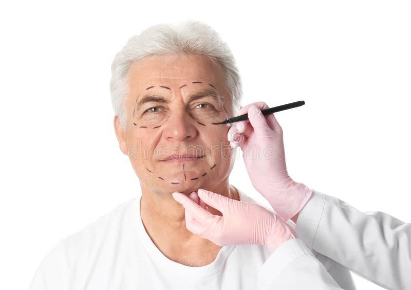 Σημάδια σχεδίων γιατρών στο ώριμο ανθρώπινο πρόσωπο για τη λειτουργία αισθητικής χειρουργικής στοκ φωτογραφία με δικαίωμα ελεύθερης χρήσης
