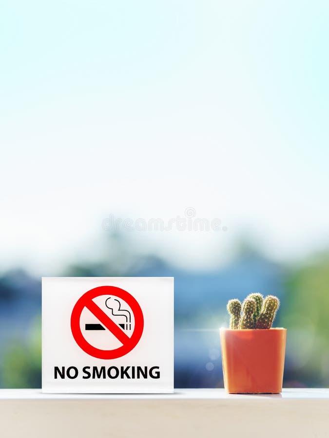 Σημάδι απαγόρευσης του καπνίσματος στο δωμάτιο ξενοδοχείου με τον κάκτο στον ξύλινο πίνακα στοκ εικόνες