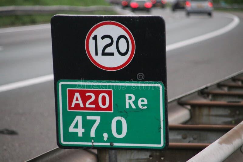 Σημάδι απόστασης στο γκούντα τίτλων αυτοκινητόδρομων A20 με το σημάδι προσοχής για την ταχύτητα στα χιλιόμετρα στοκ φωτογραφία με δικαίωμα ελεύθερης χρήσης