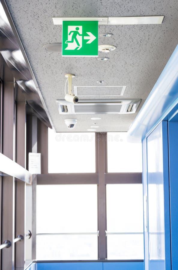 Σημάδι εξόδων lignt με το CCTV και τη κάμερα κάτω από το ανώτατο όριο για την ασφάλεια στοκ φωτογραφία με δικαίωμα ελεύθερης χρήσης