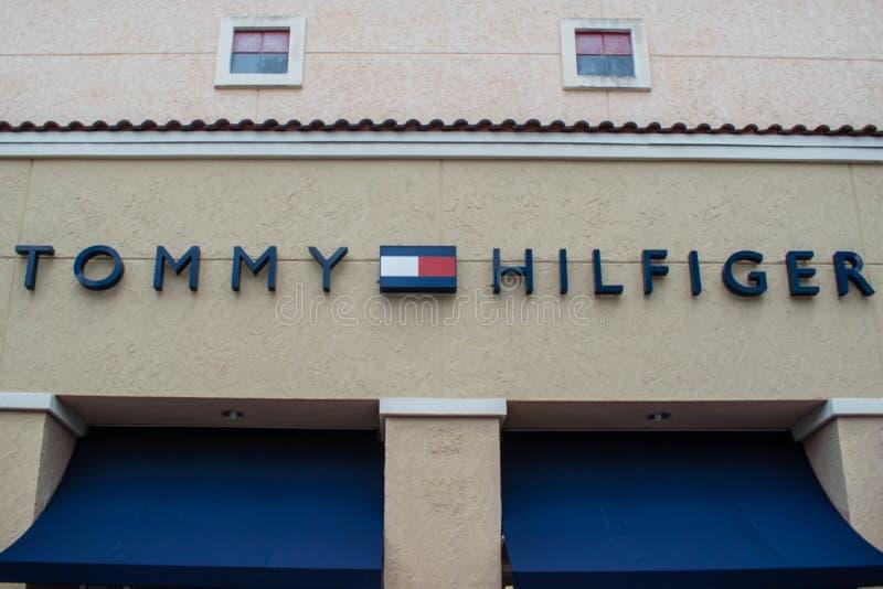 Σημάδι και λογότυπο του Tommy Hilfiger στην έξοδο ασφαλίστρου στη διεθνή περιοχή Drive στοκ φωτογραφία