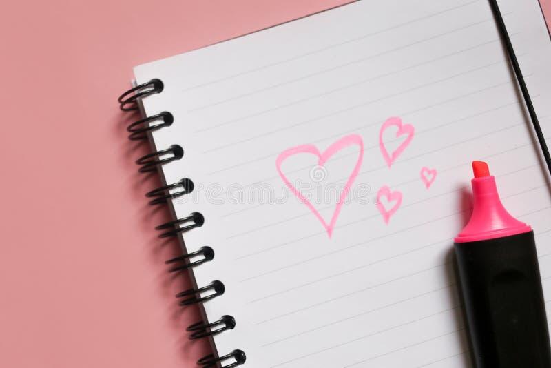 σημάδι καρδιών στο σημειωματάριο και ρόδινος δείκτης στο ρόδινο υπόβαθρο, μια σημείωση αγάπης που χρησιμοποιεί έναν ρόδινο δείκτη στοκ εικόνα