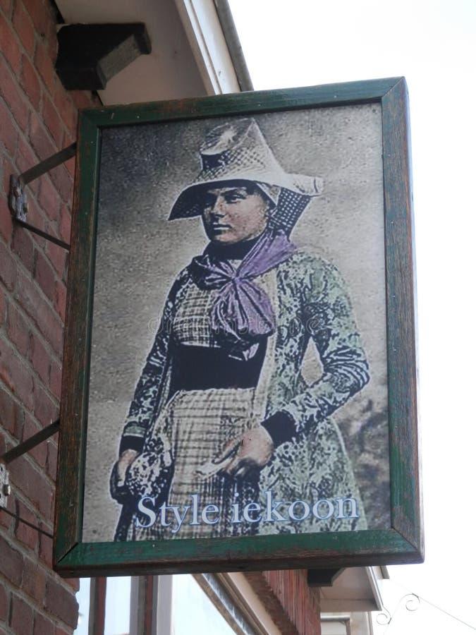 Σημάδι καταστημάτων που απεικονίζει τη γυναίκα στο παραδοσιακό φόρεμα της Φρεισίας στοκ φωτογραφίες