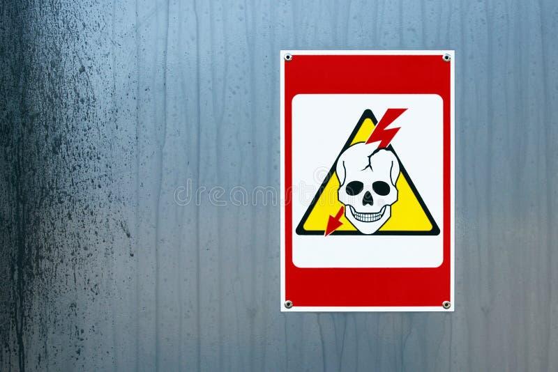 Σημάδι κινδύνου υψηλής τάσης με το ανθρώπινες κρανίο και την αστραπή στοκ φωτογραφία