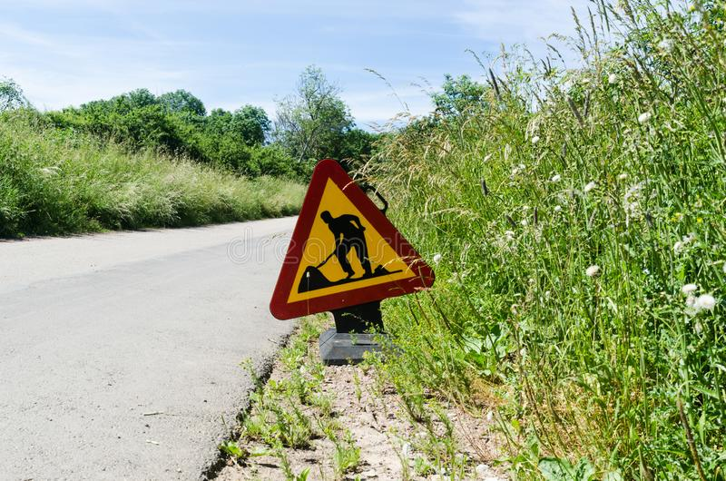 Σημάδι οδικού έργου από την άκρη του δρόμου μεταξύ της πράσινης χλόης στοκ φωτογραφία με δικαίωμα ελεύθερης χρήσης