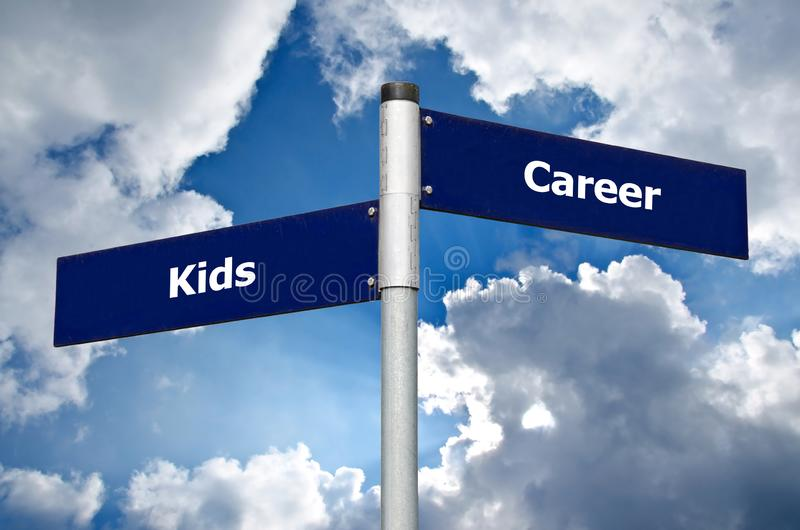 """Σημάδι οδών μπροστά από το νεφελώδη ουρανό που αντιπροσωπεύει τη δύσκολη επιλογή μεταξύ """"των παιδιών"""" και """"της σταδιοδρομίας """" στοκ φωτογραφία"""