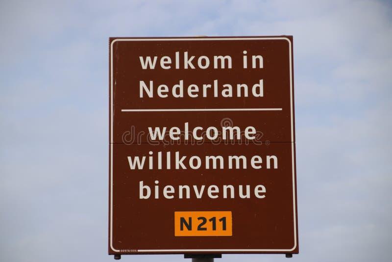 Σημάδι στα σύνορα σε 4 γλώσσες για να καλωσορίσει τους ταξιδιώτες στις Κάτω Χώρες στο πορθμείο του φορτηγού Ολλανδία Hoek στοκ εικόνα