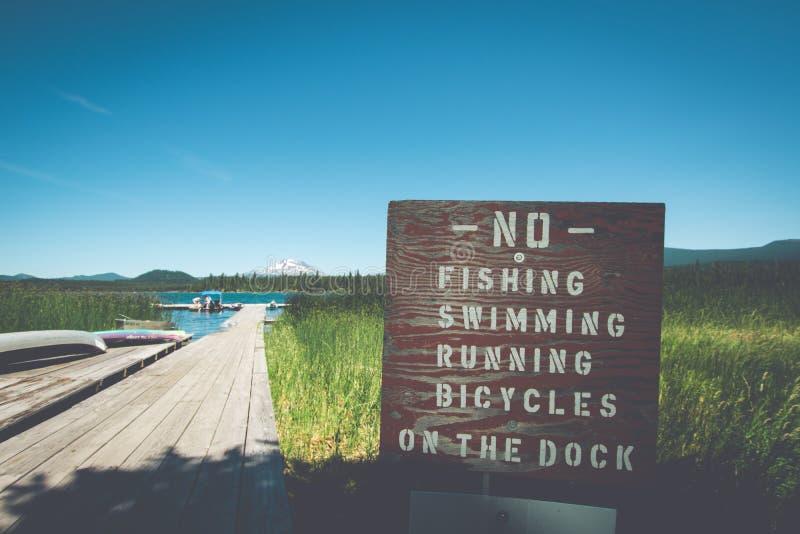 Σημάδι στη λίμνη λάβας στην κάμψη Όρεγκον που σημειώνει τους περιορισμούς - καμία αλιεία, που κολυμπά, που τρέχει, ή που στην απο στοκ φωτογραφίες με δικαίωμα ελεύθερης χρήσης