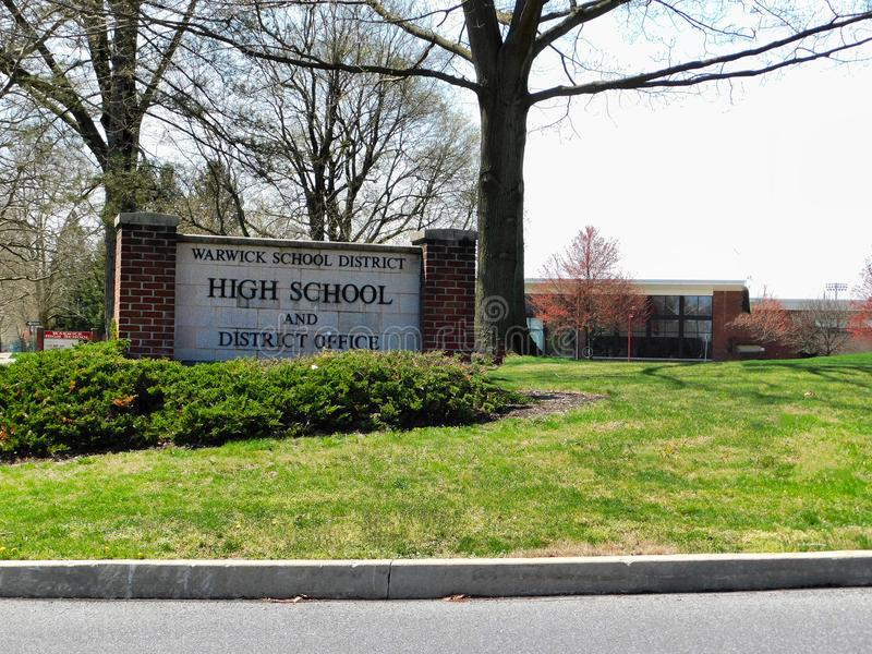 Σημάδι σχολικών περιοχών και γυμνασίου Warwick με το γυμνάσιο στο υπόβαθρο στοκ εικόνες