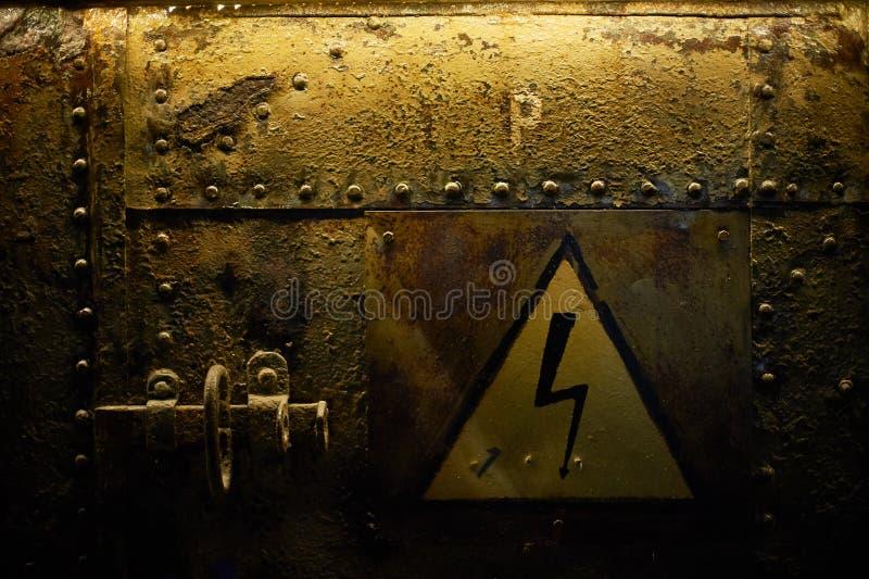 Σημάδι της υψηλής τάσης, που κολλιέται σε ένα σκουριασμένο μεταλλικό υπόβαθρο με τα καρφιά στοκ φωτογραφίες