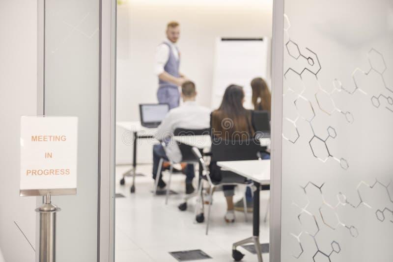 """Σημάδι """"συνάντηση υπό εξέλιξη """", στεμένος μπροστά από το γραφείο, ενώ ομάδα ανθρώπων παρουσίασης στο εσωτερικό στοκ φωτογραφία με δικαίωμα ελεύθερης χρήσης"""
