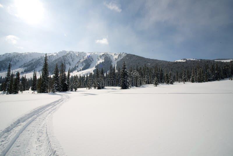 Σημάδι διαδρομής οχήματος για το χιόνι στο χιόνι ενάντια στα βουνά και έναν μπλε ουρανό στοκ εικόνες