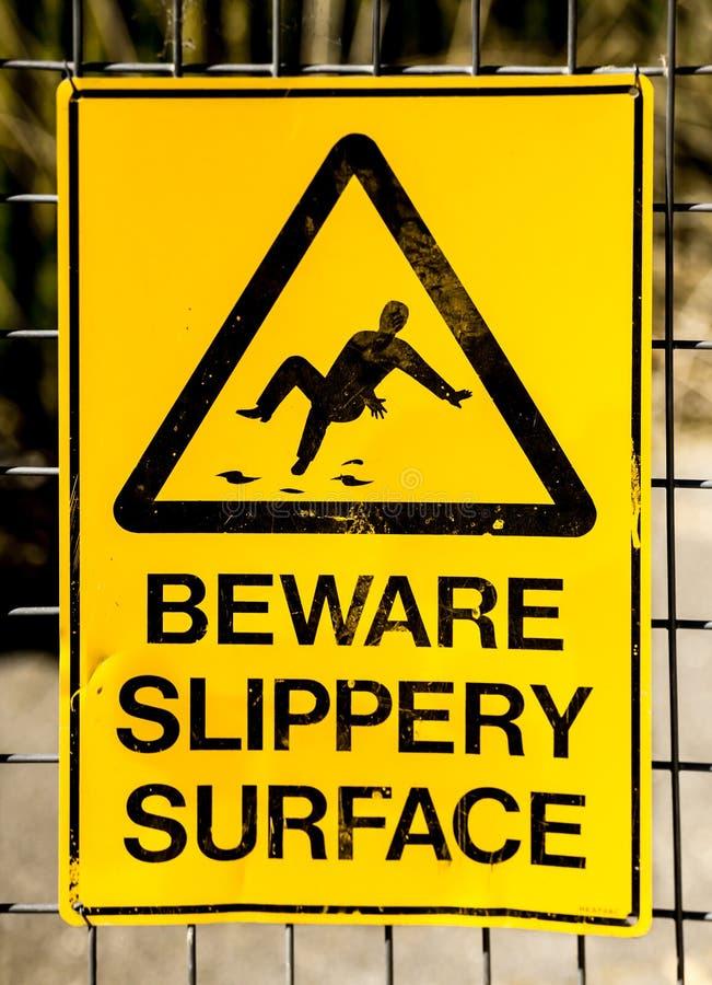 Σημάδι κινδύνου: ΟΛΙΣΘΗΡΉ ΕΠΙΦΆΝΕΙΑ BEWARE με την εικόνα της πτώσης ατόμων στοκ εικόνες