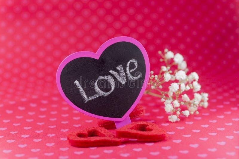 Σημάδι πινάκων κιμωλίας που λέει την αγάπη με τα λουλούδια και τις αισθητές καρδιές στο ρ στοκ φωτογραφία με δικαίωμα ελεύθερης χρήσης