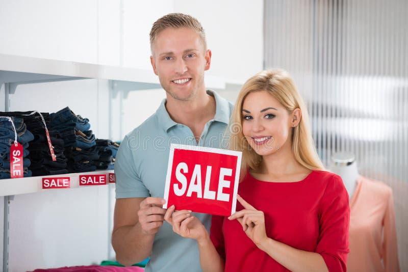 Σημάδι πώλησης εκμετάλλευσης ζεύγους χαμόγελου στο κατάστημα ιματισμού στοκ εικόνα με δικαίωμα ελεύθερης χρήσης