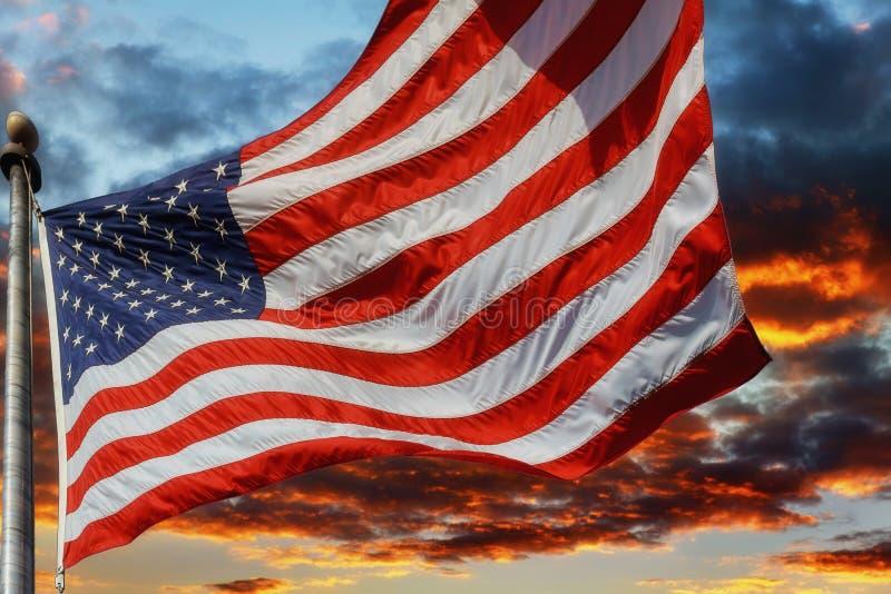 Σημαία ΗΠΑ πέρα από την όμορφη ανατολή ηλιοβασιλέματος με τα σύννεφα, στις ρόδινες και πορφυρές σκιές στοκ εικόνες με δικαίωμα ελεύθερης χρήσης