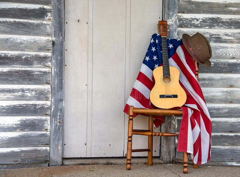 Σημαία και κιθάρα με το καπέλο στην καρέκλα στοκ εικόνες