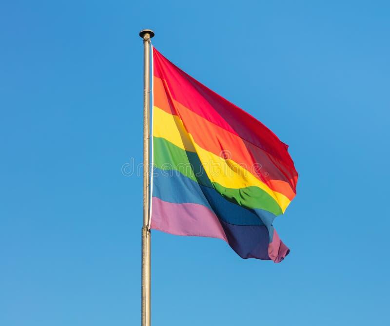Σημαία ουράνιων τόξων της μετακίνησης LGBT ενάντια στο σαφή μπλε ουρανό στοκ εικόνες