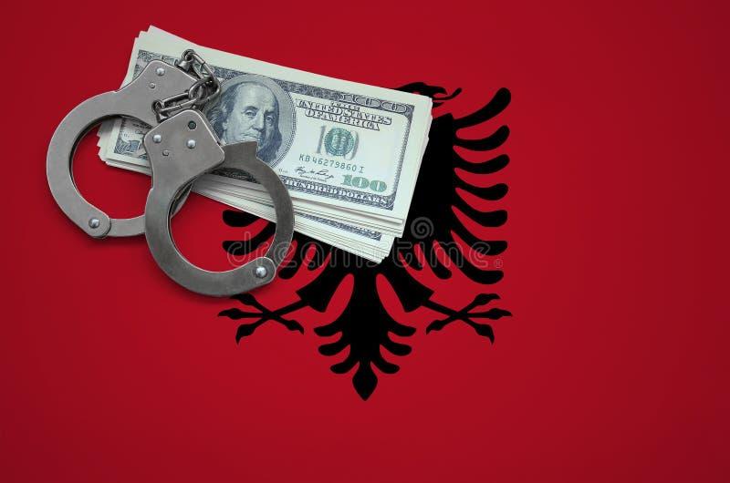 Σημαία της Αλβανίας με τις χειροπέδες και μια δέσμη των δολαρίων Η έννοια της παράβασης του νόμου και των εγκλημάτων κλεφτών στοκ φωτογραφίες