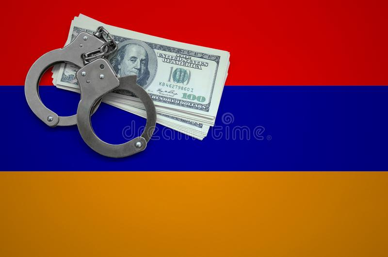 Σημαία της Αρμενίας με τις χειροπέδες και μια δέσμη των δολαρίων Η έννοια της παράβασης του νόμου και των εγκλημάτων κλεφτών στοκ φωτογραφία
