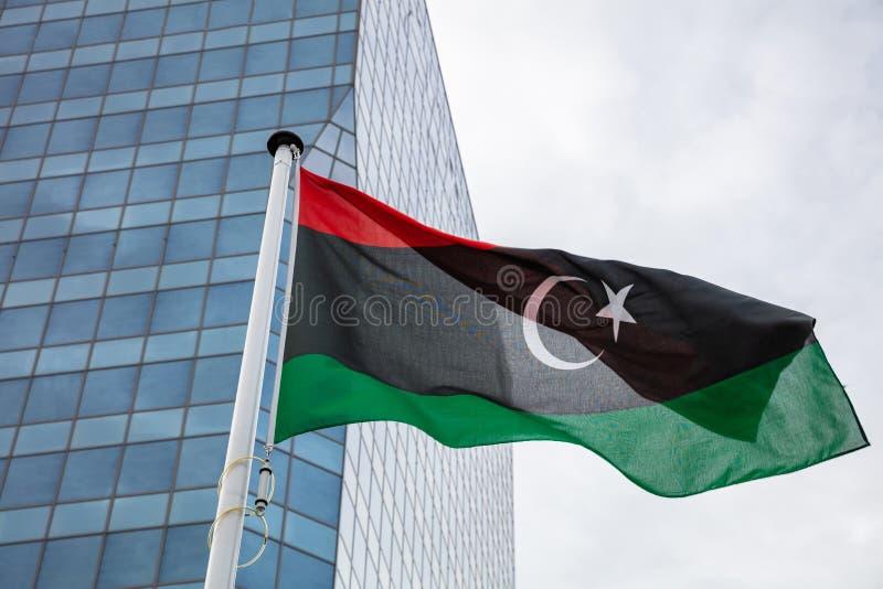 Σημαία της Λιβύης σε έναν πόλο που κυματίζει, σύγχρονο υπόβαθρο κτιρίου γραφείων στοκ εικόνες